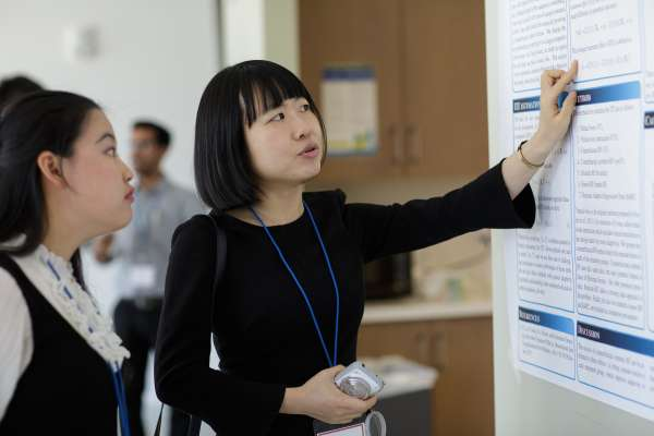 women looking at research poster